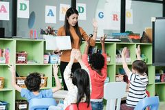 stock image of  young asian woman teacher teaching kids in kindergarten classroom, preschool education concept