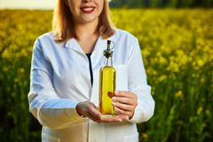 stock image of  a young beautiful biologist or agronomist examines the quality of rapeseed oil on a rape field. agribusiness concept