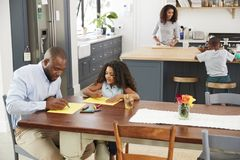 stock image of  young black family busy in their kitchen, elevated view