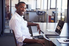 stock image of  young black man sitting at desk in office smiling to camera