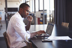 stock image of  young black man in wearing glasses using laptop in office