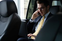 stock image of  young businessman sitting on back seat of the car, while his chauffeur is driving automobile.