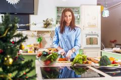 stock image of  young caucasian lady cooking new year or christmas meal in decorated kitchen at home