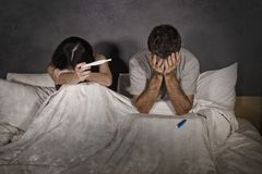 stock image of  young couple in bed scared and stressed after positive result on pregnancy test with pregnant woman expecting unwanted baby and ma