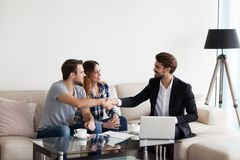 stock image of  young couple, family making deal with realtor, interior designer
