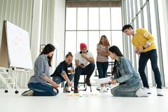 stock image of  young creative diverse group meeting and looking at project plan lay out on floor discuss or brainstorm business strategy with pos