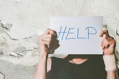 stock image of  young depressed homeless man with bandage on his hand from suicide attempt holding help sign written on paper while he leaning his