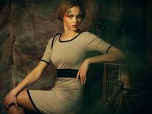 stock image of  fashion model woman with creative make up sitting on a stool in drama decoration