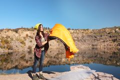 stock image of  young female camper with sleeping bag in wilderness