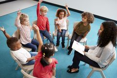 stock image of  young female school teacher reading a book to infant school children, sitting on chairs in a circle in the classroom raising hands