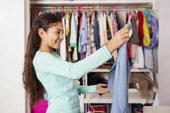 stock image of  young girl in bedroom choosing clothes from closet