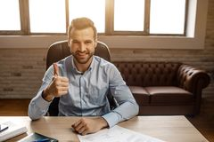 stock image of  young handsome cheerful businessman sit on table and pose in his own office. he hold big thumb up and smile. nice happy