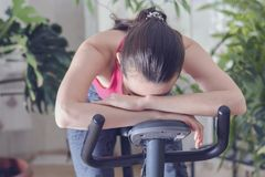 stock image of  young healthy fit woman training at home on exercise bike during work-out feeling exhausted and dizzy, lowered his head on his han