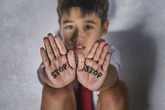 stock image of  young kid sad and depressed suffering bullying problem and abuse at school with stop word written on his hands feeling helpless in