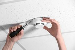 stock image of  young male technician installing smoke alarm system