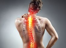 stock image of  young man holding his neck in pain.