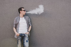 stock image of  young man smoking, vaping electronic cigarette or vape. gray background