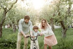 stock image of  young mom and dad teach their son to ride a bike