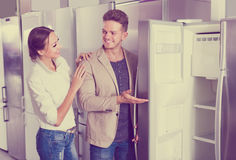 stock image of  young positive couple choosing new refrigerator in hypermarket