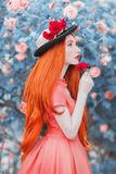 stock image of  young redhead girl feels a bright sense from the smell of flower in garden. very long hair. bright rose background