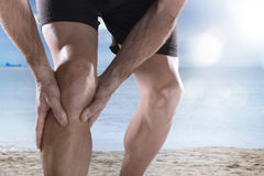stock image of  young sport man with athletic legs holding knee in pain suffering muscle injury running