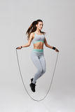stock image of  young sportive beautiful girl doing exercises with jumping rope over white background.