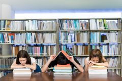 stock image of  young student group reading book serious, hard exam, quiz, test sleeping headache worry in classroom education library university