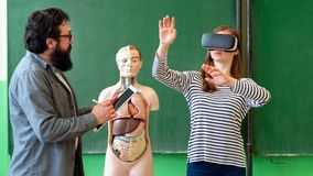 stock image of  young teacher using virtual reality glasses and 3d presentation. education, vr, tutoring, new technologies and teaching methods.