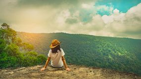 stock image of  young traveling woman wearing hat and sitting on the top of the mountain cliff with relaxing mood. asian woman travel alone.