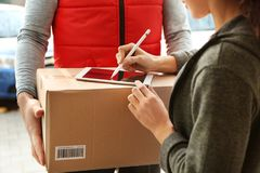 stock image of  young woman appending signature after receiving parcel