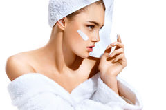 stock image of  young woman with flawless skin, applying moisturizing cream on her face.