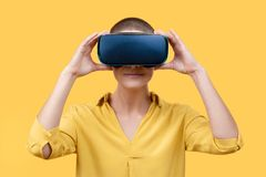 stock image of  young woman in her 30s using virtual reality goggles. woman wearing vr glasses isolated over yellow background. vr experience.