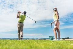 stock image of  young woman practicing the correct move during golf class