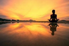 stock image of  young woman practicing yoga in the nature, female happiness, silhouette of young woman practicing yoga on the beach at sunset