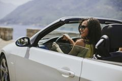 stock image of  young woman with sunglasses driving her convertible top automobile on bright sunny day