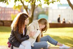 stock image of  young woman support and soothe her upsed friend. two girl during the conversation