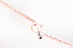 Taśmy miara wokoło lampy Fotografia Stock