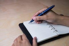 Ta anmärkningen på anteckningsboken vid den blåa bollpennan arkivfoto