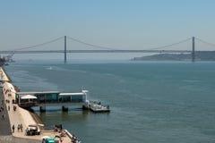 25ta April Bridge en Lisboa y embarcadero con la gente, Portugal Imagen de archivo