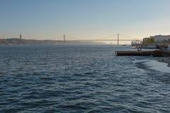 25ta April Bridge en Lisboa y un par en el embarcadero de Wodden Fotos de archivo