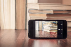 Ta bilden av gamla böcker med smartphonen royaltyfri illustrationer