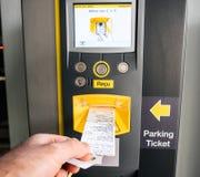 Ta biljetten och fakturan ut från att parkera maskinen arkivbild