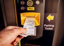 Ta biljetten och fakturan ut från att parkera maskinen royaltyfria bilder