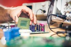 Ta bort CPU från huvudsakligt strömkretsbräde för att kontrollera problem och reparation Royaltyfri Foto