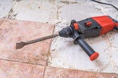 Ta bort gamla tegelplattor Tryckluftsborr - borranderivninghammare på golv royaltyfri foto