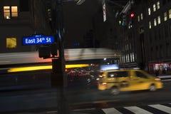 34ta calle Nueva York del autobús del taxi móvil del nyc en la noche Foto de archivo