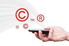 Ta copyrightt på varumärkessymboler som flyger från smartphone Royaltyfri Fotografi