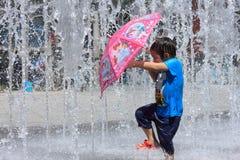 ta den röda umbrelflickan som leker vid vattenspringbrunnen Arkivfoton