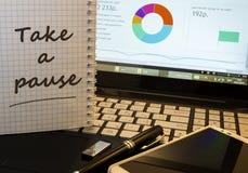 Ta en paus i notepad på kontorsarbetsplats Royaltyfri Bild