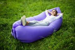Ta ett avbrott Den nätta unga kvinnan som ligger på uppblåsbar soffalamzac, medan vila på gräs, parkerar in på solen arkivbilder